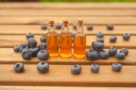 Essence of blueberry on a Wooden  background in a beautiful glass jar