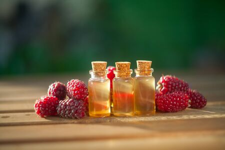 Essence of Wild raspberries  on a table in a beautiful glass Bottle Imagens