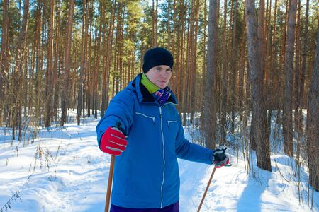 handsome man with skis in the winter forest