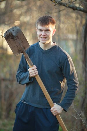 Agronomist handsome strong man with shovel on the background of flower beds