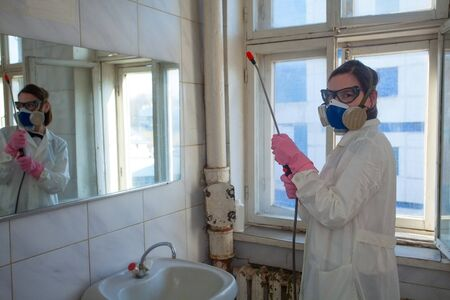 employee in a suit sprays the room from infection