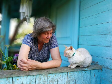 country woman with beautiful cat on a blue porch