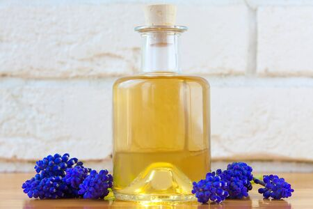 Essential oil of a muscari flower on a table in a beautiful bottle