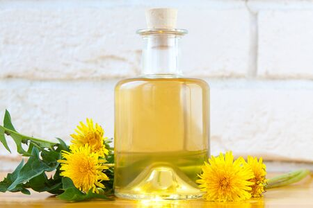 dandelion essential oil in a beautiful bottle on the table