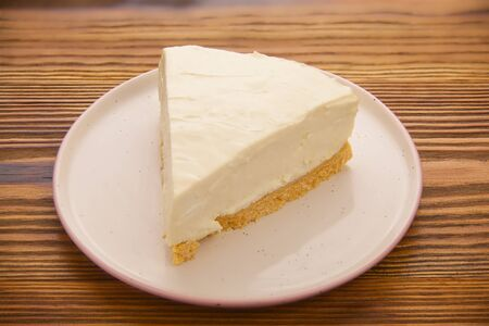 classic cheesecake on a white plate on a wooden table