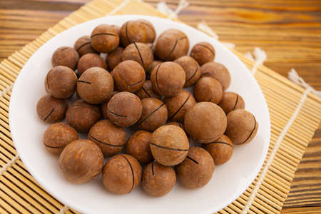 delicious macadamia nuts on a plate on a wooden background