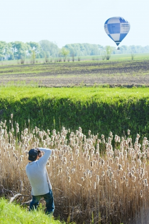 man photographs the balloon, which flies over a field photo