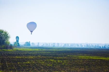 balloon, which flies over a field photo