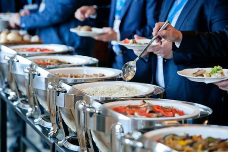 mannen in blauwe pakken kiezen van voedsel bij een banket