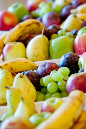 pears, bananas, plums, apples, grapes lying on white plates