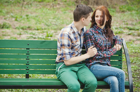 love at first sight: Flirting young couple in plaid shirts sitting on a bench in the park Stock Photo