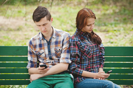 A young couple sitting in a park on a bench looking each into their mobile phone and looking away from each other