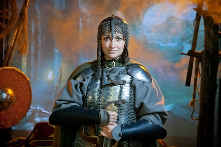 A woman dressed in chain mail with a sword in her hands against the background of of the castle, weapons and mountains in the distance