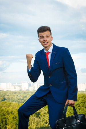 Cheerful busiessman who made a good deal dressed in blue suit and red tie with a briefcase in his hand against the backdrop of the city and the sky