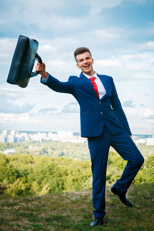 Cheerful laughing businessman who made a good deal dressed in blue suit and red  tie waving briefcase against the backdrop of the city and the sky
