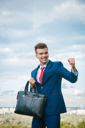 Empresario sonriente alegre que hizo un buen negocio vestido con traje azul y corbata roja con un maletín en la mano en el contexto de la ciudad y el cielo