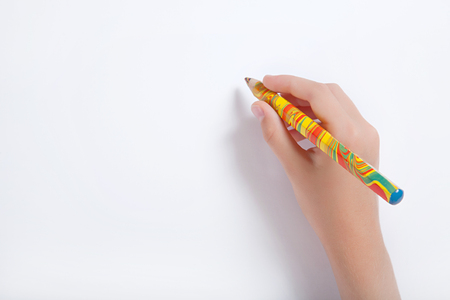 The childs hand holding a multicolored pencil against a white sheet of paper