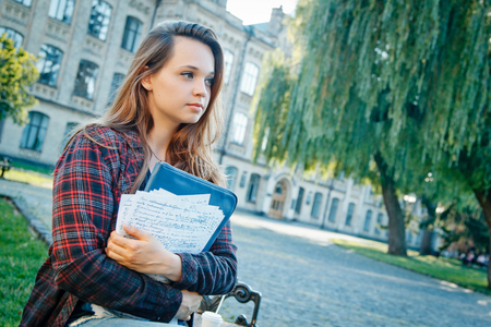 beautiful girl student sitting on bench near university