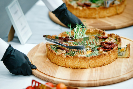 Hands of a waiter in black gloves putting pies with sprouts on top, chopped into pieces with metal tongs on the banquet table where there are already other pies Standard-Bild