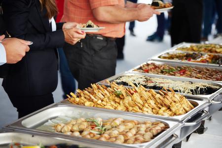 Männer in blauen Anzügen, die bei einem Bankett Essen auswählen