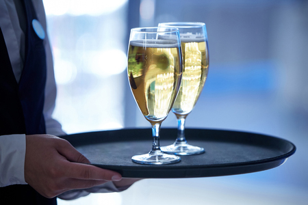 Die Hände eines Kellners in einer schwarzen Weste und einem weißen Hemd mit zwei Gläsern Champagner auf einem Tablett holding