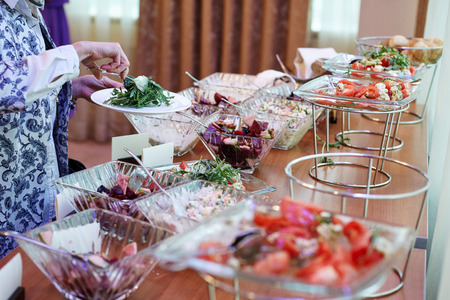 The hands of the woman taking food with covered with greens and salads banquet table at the conference
