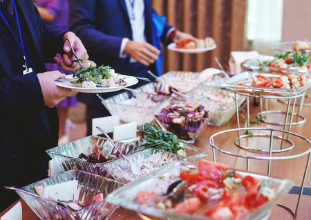 The hands of people taking food with covered with greens and salads banquet table at the conference Stock Photo