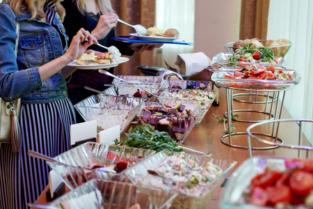 The hands of women taking food with covered with greens and salads banquet table at the conference