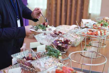 The hands of the man taking food with covered with greens and salads banquet table at the conference