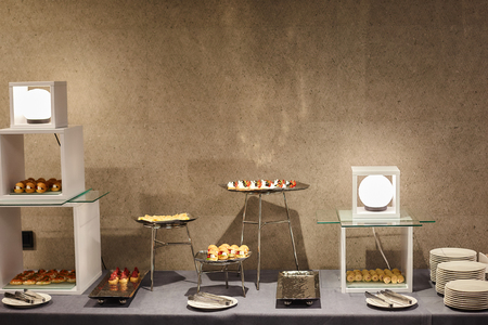 Various snacks on a modern banquet table covered with a gray tablecloth, illuminated by round lamps against a gray wall