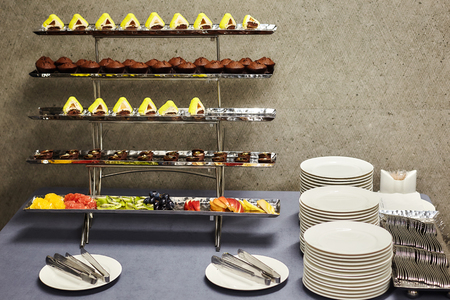 Desserts, fruits, piles of white plates and cutlery at the banquet table