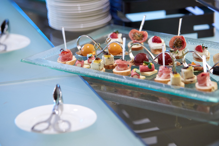 A variety of canapes lying on a glass tray