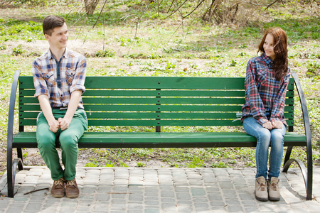 Flirting young couple in plaid shirts sitting on a bench in the park