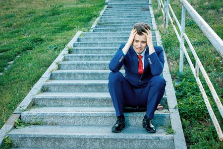Weeping young attractive businessman clasping his head in his hands dressed in a blue suit with a red tie sitting on the stairs with a rusty railing Imagens