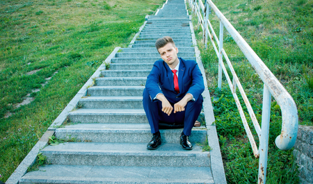 Sad young attractive business man dressed in a blue suit with a red tie sitting on the stairs with a rusty railing