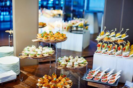 Canned wooden buffet table with various canapes lying on trays with mirrors in the background