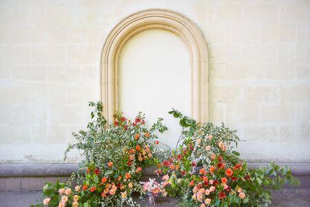 wedding flower arch near an old wall