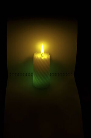 A burning candle on the background of an open note