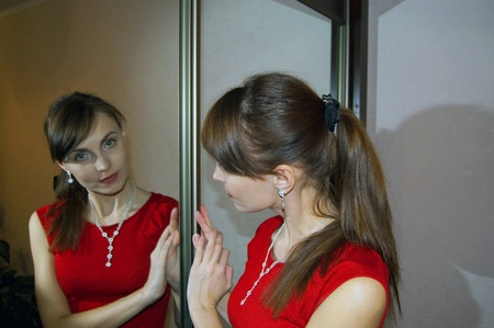 The girl in red dress in front of a mirror closet door  photo