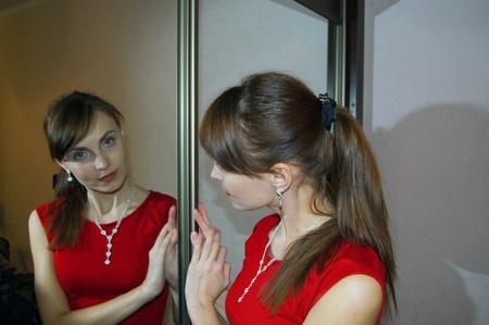 closet door: The girl in red dress in front of a mirror closet door  Stock Photo