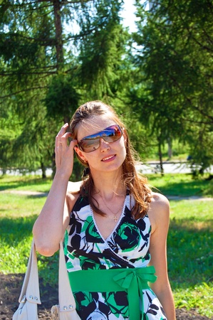 A woman in sunglasses on the background of nature. Summer sunny day. Stock Photo