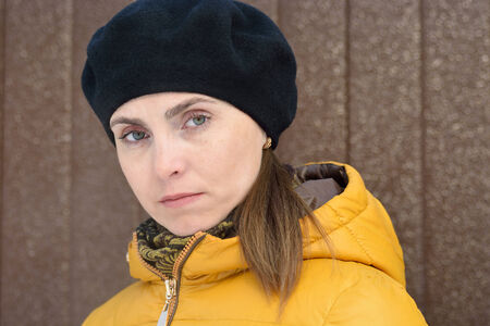 frowns: Woman in black beret and a yellow jacket with a hood on a brown background  Frowns  Stock Photo