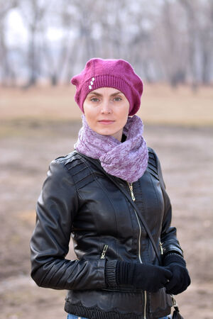 Woman in red beret and black leather jacket in the park