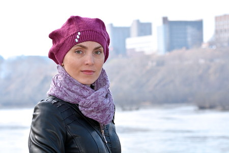 Woman in a red beret and a black jacket on a background of the river and city