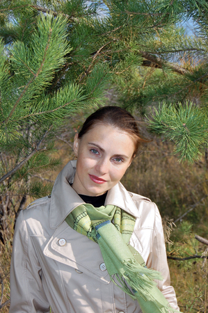 Portrait of a woman in a raincoat on a background of pine branches