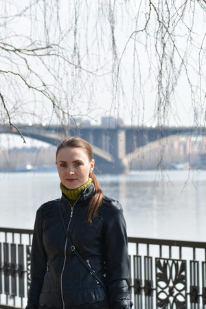 Woman in front of a metal fence on the background of the river and bridge