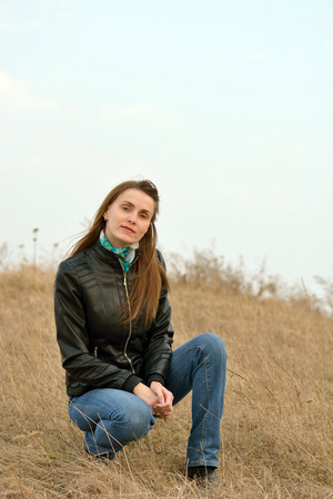 Woman in jeans on the background of dry grass and blue sky