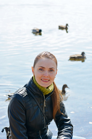 Woman against lake with ducks
