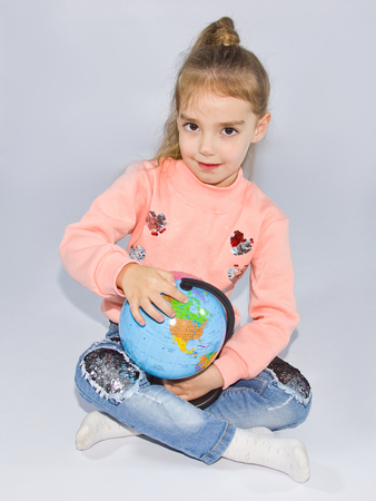 little girl sits and holds a small globe