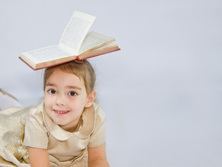 little girl is holding a book Imagens